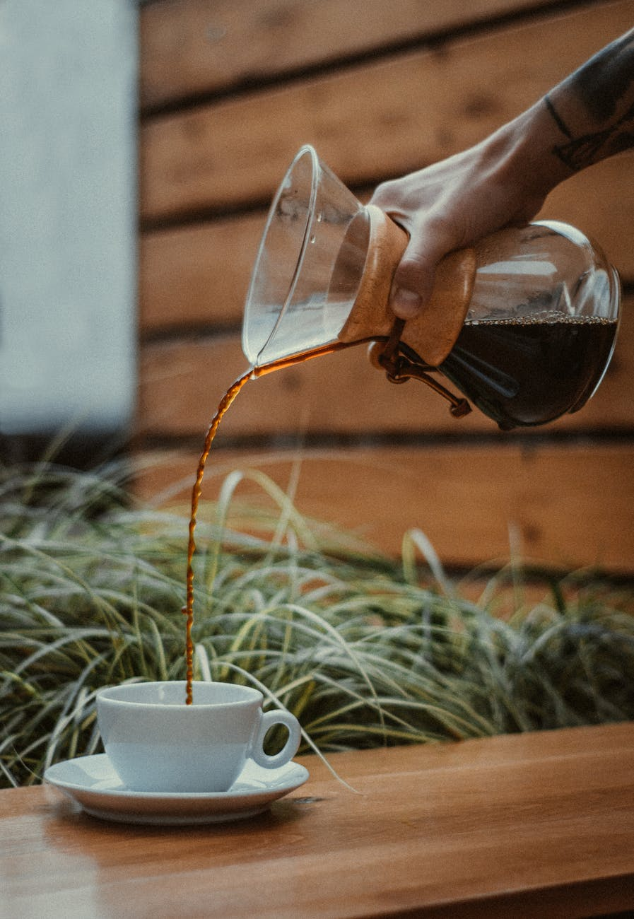 a person pouring coffee into a cup