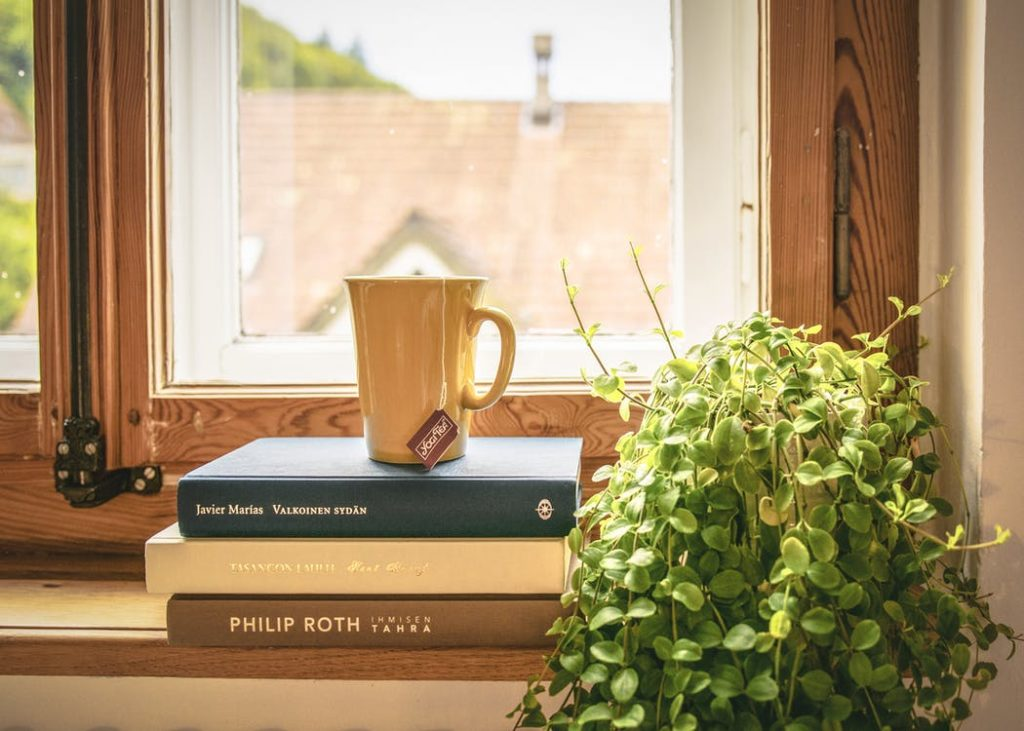 Image of books stacked on a windowsill.